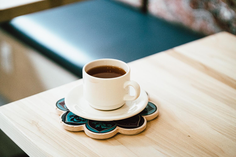 A mug of botte chai coffee sits atop a coaster at Botte Chai Bar in Saskatoon Saskatchewan.