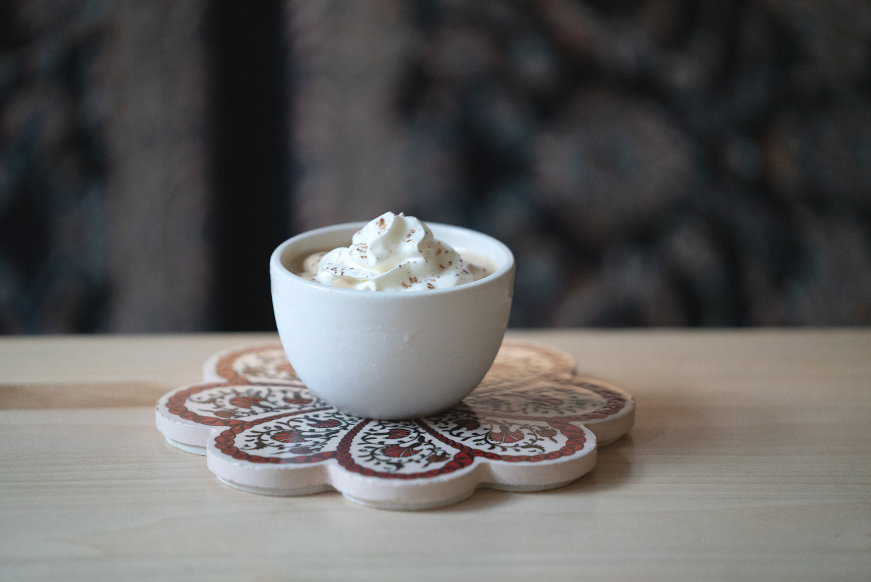 A cup filled with a botta chai latte sits atop a floral designed coaster at Botta Chai Bar in Saskatoon Saskatchewan.