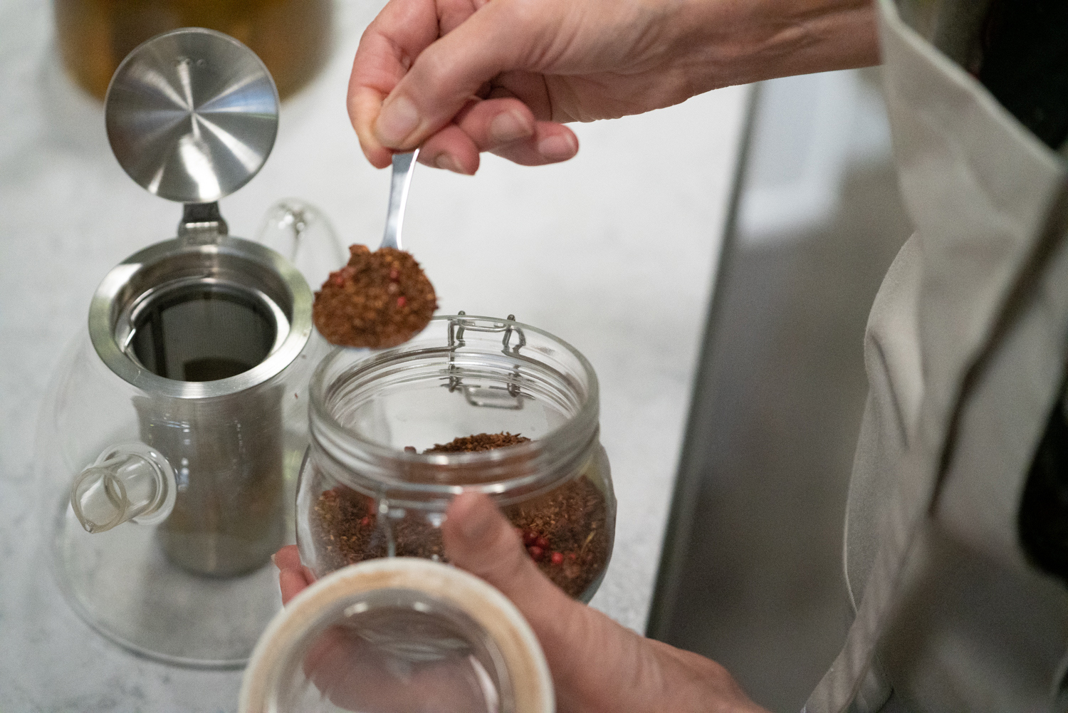 A staff member scoops tea leaves into a container to prepare tea at Botte Chai Bar in Saskatoon Saskatchewan.