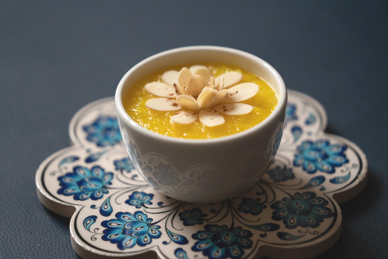 An edible flower floats atop a yellow soup at Botte Chai Bar in Saskatoon Saskatchewan.