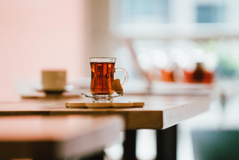 A mug of botte chai tea sits atop a coster at an empty table in Botta Chai Bar of Saskatoon Saskatchewan. Across the table, a smaler mug can be seen.