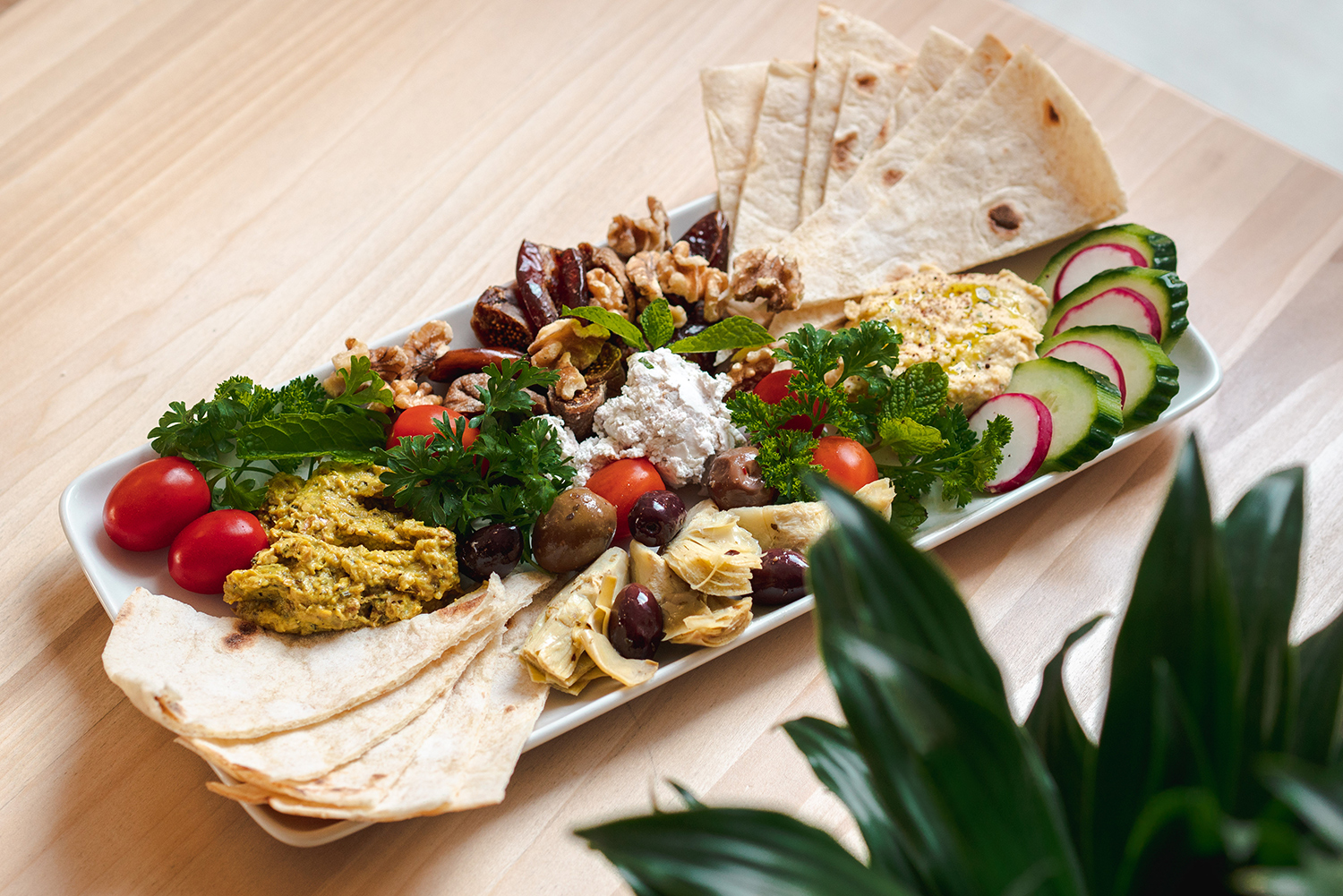 A mezze platter sits on a table at Botte Chai Bar in Saskatoon Saskatchewan. The platter has cucumber and radish slices, pita bread, olives, grape tomatoes, hummus, kale, and a varity of dips and nuts.